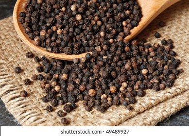 Black peppercorns spilling from wooden spoon onto burlap.  Macro with shallow dof.