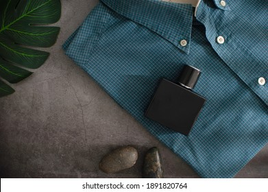 A black perfume bottle placed on a shirt on a cemented background.