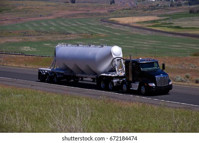 Black Peterbilt Semi pulling a silver unmarked tanker trailer. June 20th, 2017 Oregon, USA