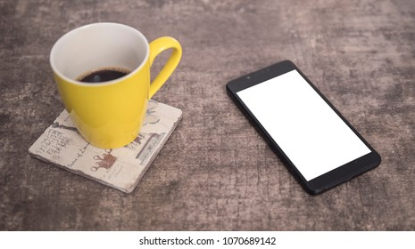 Black phone on a wooden table next to yellow cup of coffee mock up