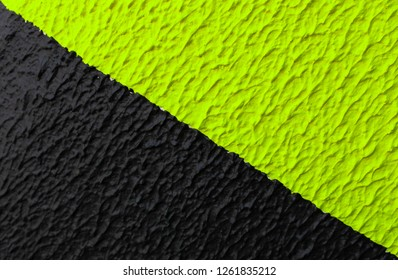 Black and phosphorus green diagonal strip caution sign. Striped black and green paint wall texture. Striped diagonal safety pattern Background slanted lines The background for printing, wallpapers or
