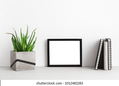 Black photo frame, books and a plant in concrete flowerpot. Mock up.
