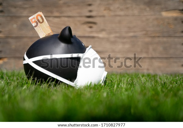 Black piggy Bank on the Meadow with Money. The Background Wood Wall