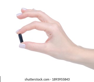 Black pill capsule in hand on white background isolation