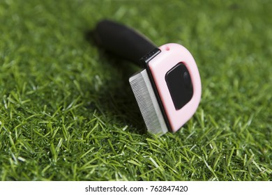 Black with pink furminators for cats on the background of artificial grass