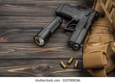 black pistol, flashlight and cartridges on a brown wooden background
