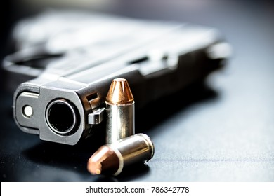 A black pistol hand gun with bullets.