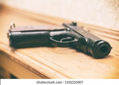 Black pistol on a light wooden background