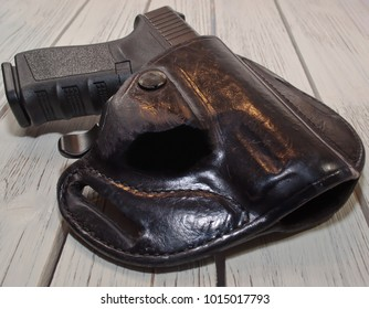 A black  pistol shown in a holster laying on a wooden table