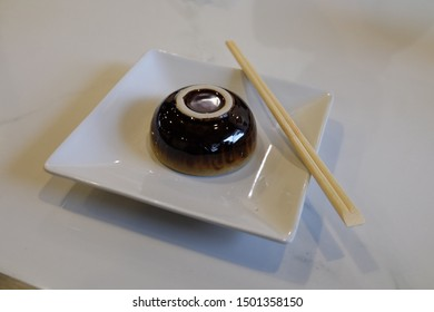 The black bowl​ is placed in a square white plate and has a wooden chopstick beside it.