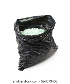 Black plastic bag full of bioplastic packing foam peanuts isolated over the white background