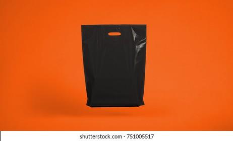Black plastic bag on an orange background