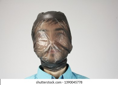 black plastic bag wraps around a human head, gray background, concept of suffocating person, big ecology problem pollution, copy space