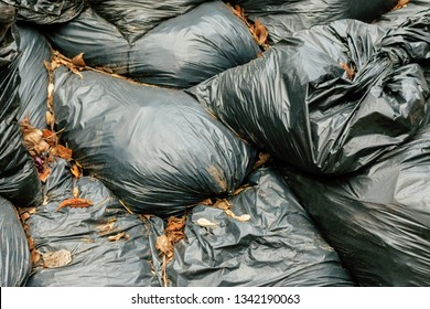 black plastic bags with garbage and orange leaves lie on each other. Plastic Bags pile junk garbage Trash background. threat of pollution of the planet concept