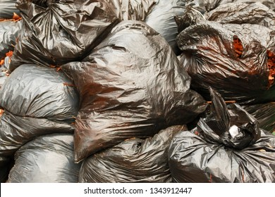 black plastic bags with orange autumn leaves. Black Trash Bags Litter Garbage close-up background. Nature ecology problem concept