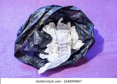 A black plastic bin bag with screwed up used tissues and empty tablet blister packs