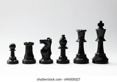 Black plastic chess pieces in a row on white background. Pawn, rook, knight, bishop, queen, king. Two-player strategy board game.