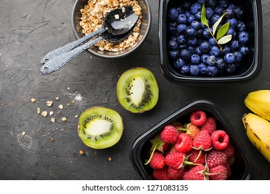 Black plastic containers take-away for a healthy snack food with raspberries, blueberries. Ingredients of healthy breakfast: granola, oat flakes, berries, nuts, apples, bananas. Top View