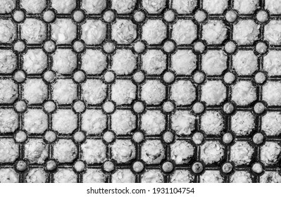 Black plastic grate is pressed into the white snow. Mesh pattern, circles on knots. Winter background concept.