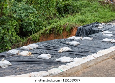 Black plastic with sandbag covered on collapsed road in valley