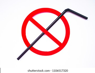 Black plastic straw set up in a red prohibition circle over a white background, telling a campaign of ban on it for an environmental concern