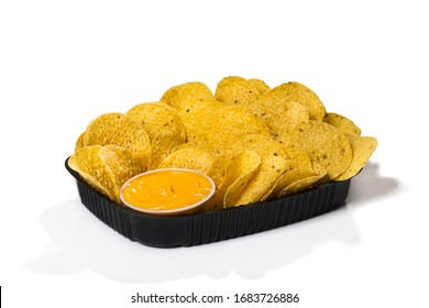 Black plastic tray of round yellow nachos with melted cheese dip on white background isolated