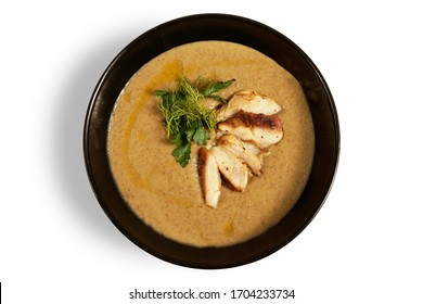 Black plate with cream soup with mushrooms on gray background minimalism