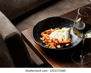 Black plate with creamy burrata and carrots and wine glass on table in a restaurant
