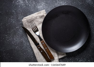 Black plate, cutlery and napkin on stone table top view. Table setting.