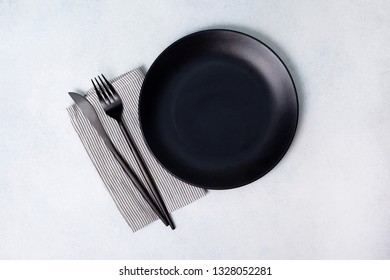 black plate and cutlery on a light background. view from above
