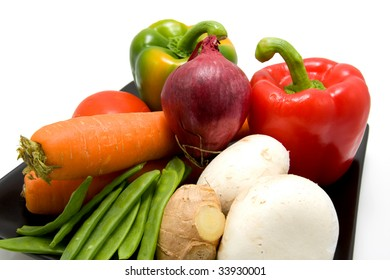 Black plate with different vegetables over white background