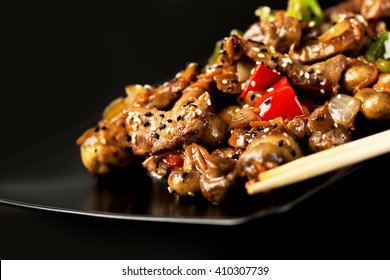 Black plate with meat and vegetables covered with sesame seeds
