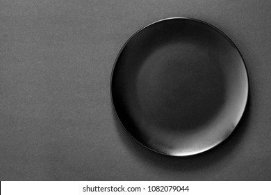 Black plate on a black background. Flat lay, top view, copy space