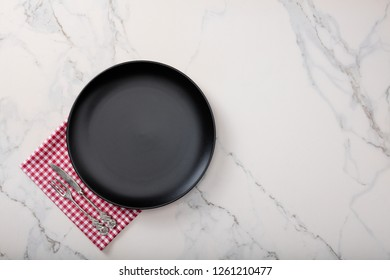 Black plate on marble countertop with red plaid napkin.