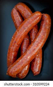 A black plate with a pile of raw North African  Merguez sausages.