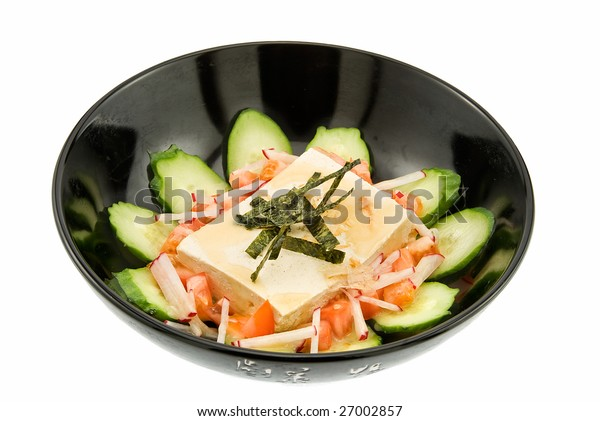 black plate of salad with tofu on white background