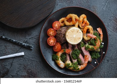 Black plate with surf and turf meal over grey cracked stone background, view from above, horizontal shot
