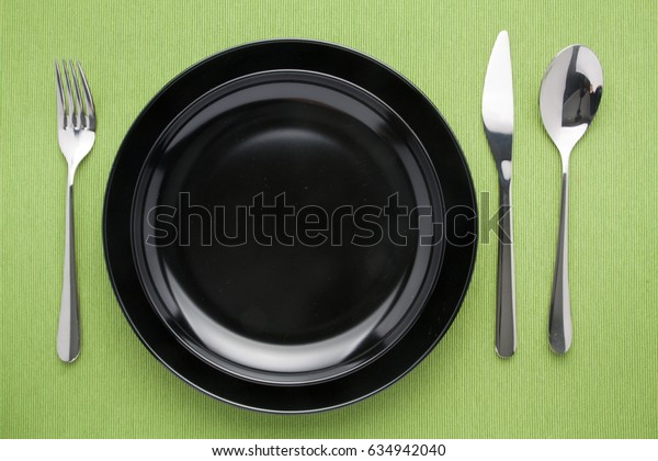 black plate in table knife and fork spoon on napery