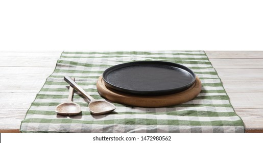 Black plate or tray, or pizza board, with tablecloth on wooden table. Top view mock up