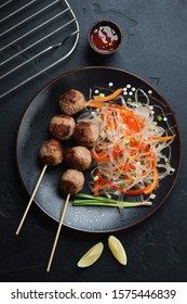 Black plate with vietnamese nem nuong and pho noodles, vertical shot over black stone background, flatlay