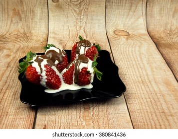 Black plates with four fresh strawberries with cream and hot chocolate on the table with wooden planks. Side view. Horizontal.
