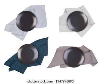 Black plates with napkins isolated on white background, top view
