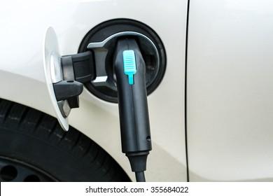 Black plug is charging an electric car