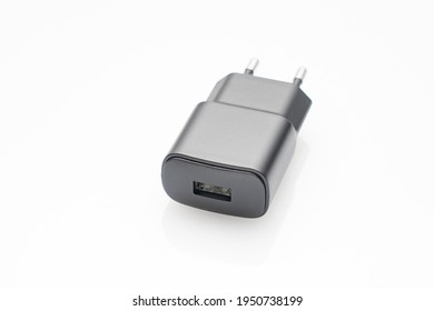 black plug of the USB adapter on a white background, adapter for charging gadgets from the 220 volt electrical network