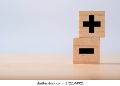 Black of plus and minus sign in on wooden cube.