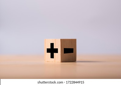 Black of plus and minus sign in opposite side of wooden cube.