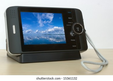 Black pocket multimedia viewer on wooden desk