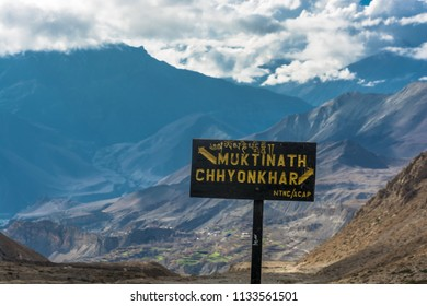 Black pointer to the fork in the road in Muktinath and Chhyonkhar on a background of mountains and clouds, Nepal.