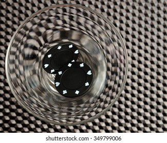 Black poker chips on a black background