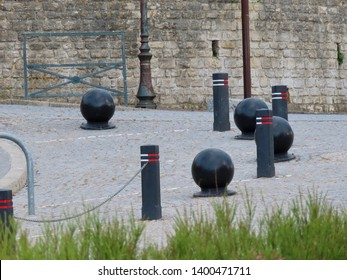 Black poles and balls marking the border between sidewalk and road, vintage looks, cobbled street, grey stone block wall.